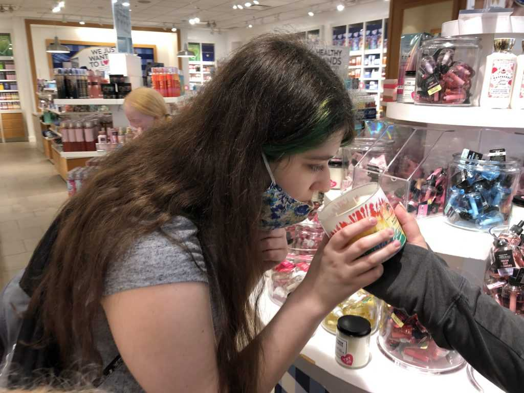 A girl holds a jar candle to her face in order to smell it