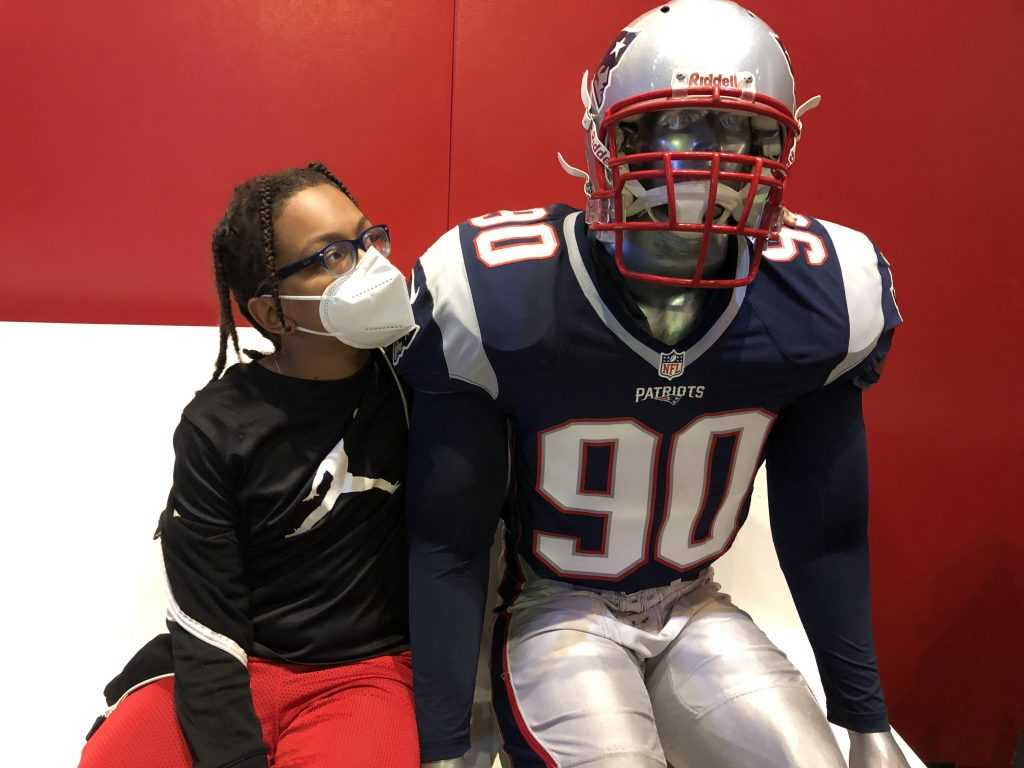 A boy sits next to a mannequin dressed as a Patriots football player while sitting on a bench