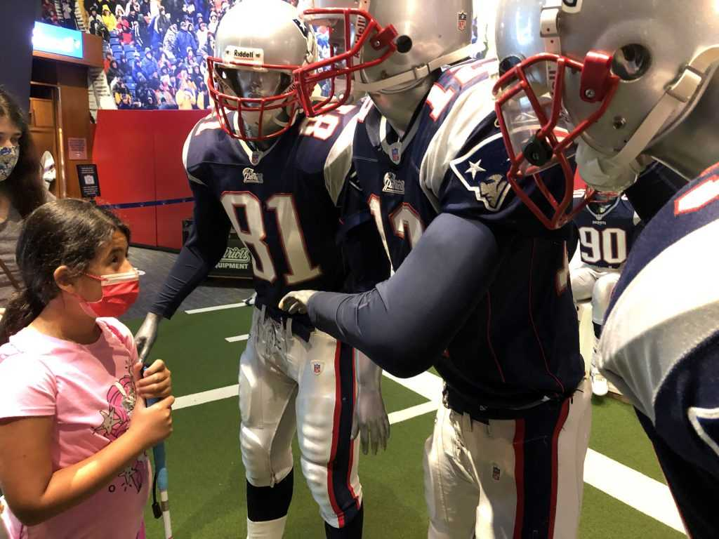 A girl looks up at three mannequins dressed as Patriots football players who are standing as if in a huddle
