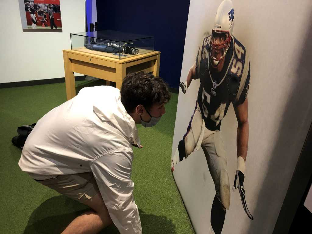 a young man assumes the three point football stance while facing the picture of a football player