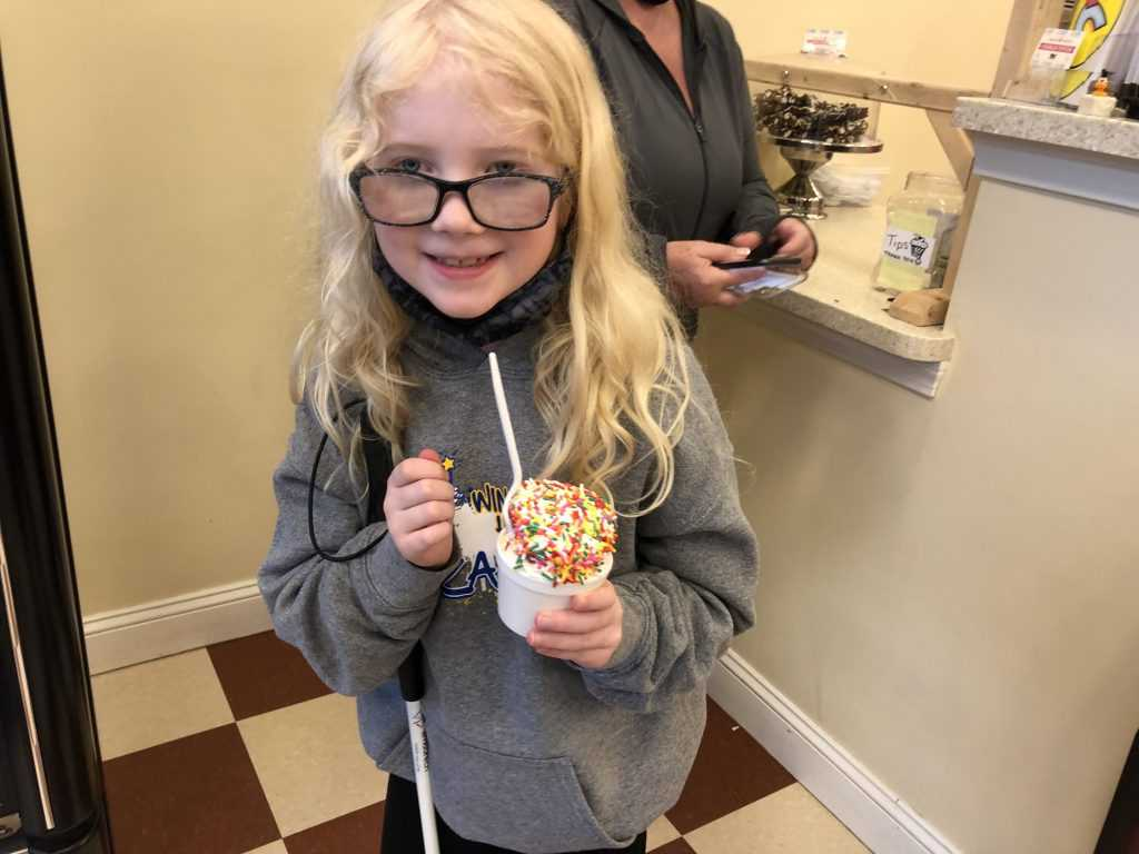 A girl stands with a cup of ice ream that has colored jimmies and a spoon